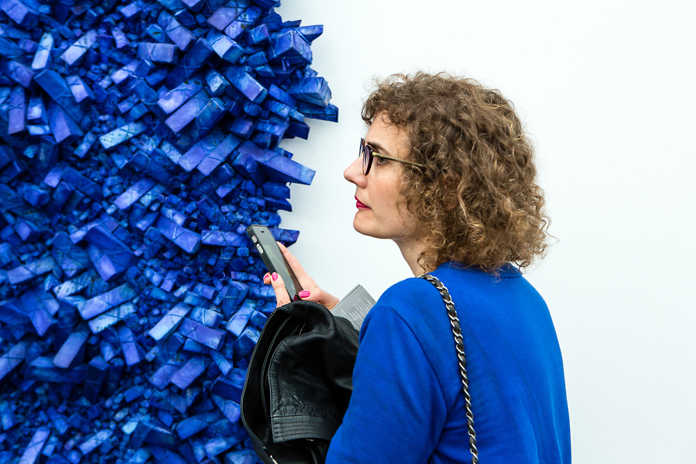 "New York, NY - 5 May 2017. The opening day of the Frieze Art Fair, showcasing modern and contemporary art presented by galleries from around the world, on Randall's Island in New York City. A woman whose sweater closely matches the color of Kwang Young Chun's piece, part of a series of ""Aggregations,"" in the PKM Gallery from Seoul."