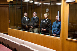 Defendant in the dock with security staff