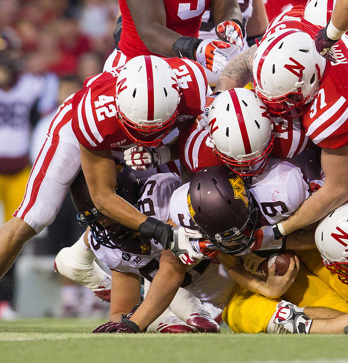 Philip Nelson #9 of the Minnesota Golden Gophers finds himself buried by the Blackshirts during Nebraska's 38-14 win over the Gophers on Nov. 17, 2012 at Memorial Stadium.