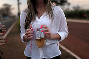 A cowgirl drinks beer from a boot shaped glass before attending a stadium where a rodeo competition is performed in Barretos during the Barretos Rodeo Fair in  Sao Paulo state, Brazil, Thursday, Aug. 23, 2012. Brazil is on a quick path to become a global power. Rising economy, big infrastructure projects, an emerging and eager consuming middle class and the booming national industry are the evidences and consequences of the wealth in the southern nation. But the often hidden source of all this wealth falls far from the luring Rio beaches or the Kolkata-New York mix that Sao Paulo is. Behind texan hats and a similar attitude the countrymen display their power through a myriad of projects, festivals and behavior visually analyzed here.
