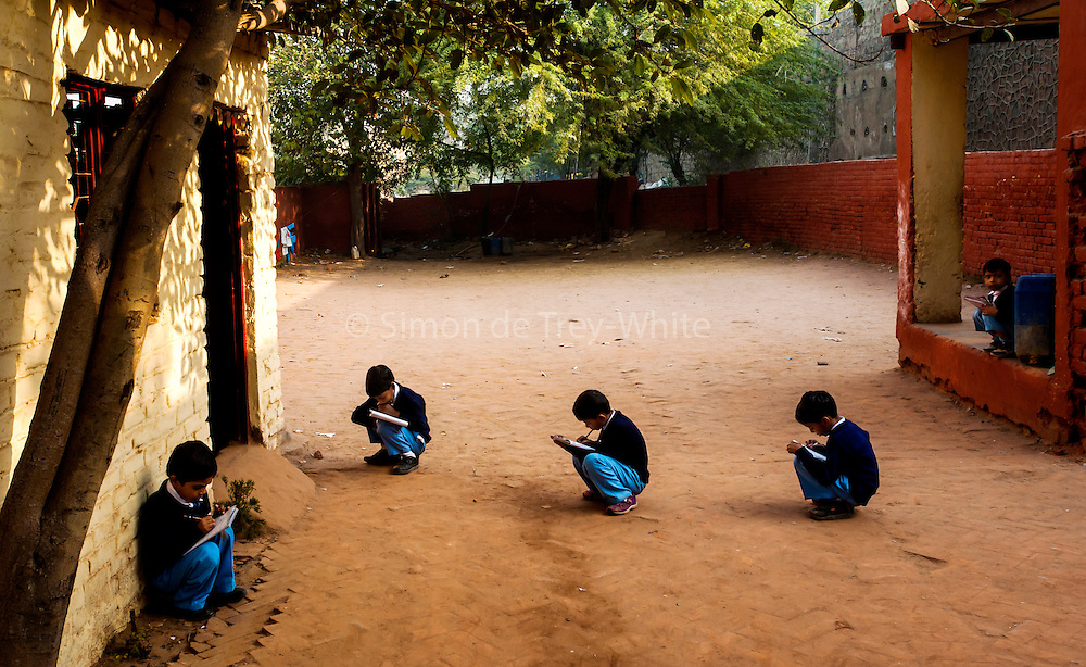 Naughty pupils banished to the outdoors to study at the Greenfield Paramount School, Kusumpur Pahari Slum, near Vasant Vihar, South West Delhi, 27th November 2009<br /> <br /> PHOTOGRAPH BY AND COPYRIGHT OF SIMON DE TREY-WHITE a photographer in Delhi<br /> <br /> + 91 98103 99809<br /> email: simon@simondetreywhite.com