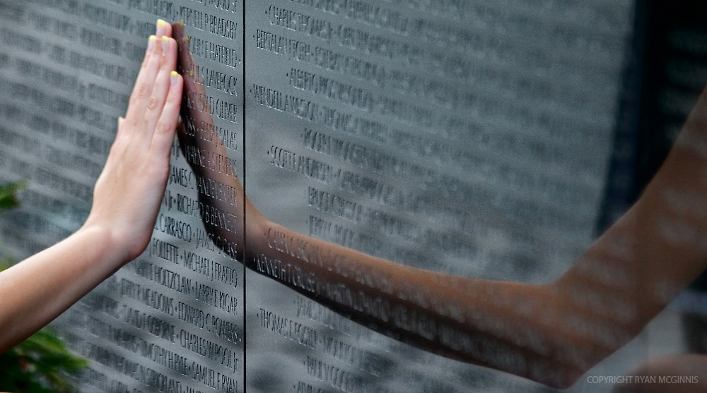 A woman touches the Vietnam War Memorial in Washington, D.C., June 13, 2006.