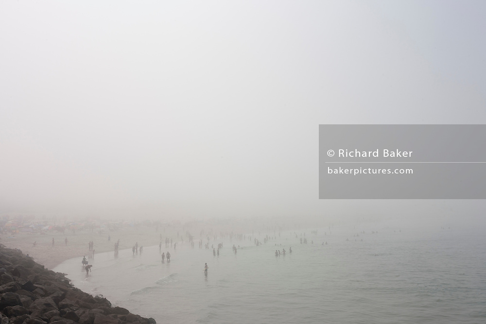 During a summer sea fog that has swept along this part of the Portuguese coast, misty sunbathers and sea swimmers enjoy cooler temperatures, on 18th July 2016, at Barra, near Aveira, Portugal. The faint figures disappear into the distance as the mist rolls across the beach. (Photo by Richard Baker / In Pictures via Getty Images)