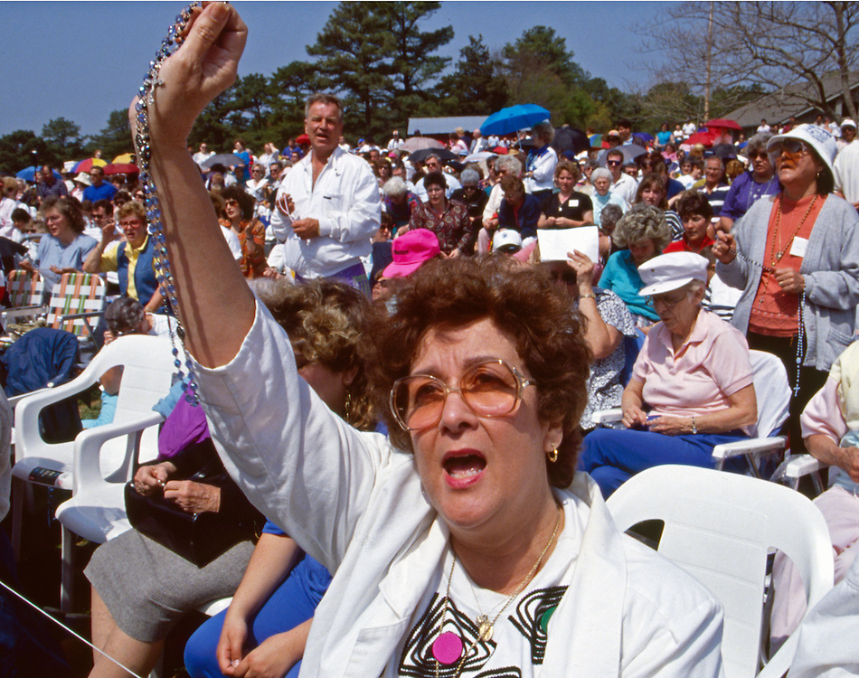 A Pilgrim Holds a Rosary Aloft During Nancy Fowler's Message from Mary.<br />