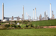 Houses dwarfed by huge oil refinery works near Pembroke, Pembrokeshire, Wales, UK