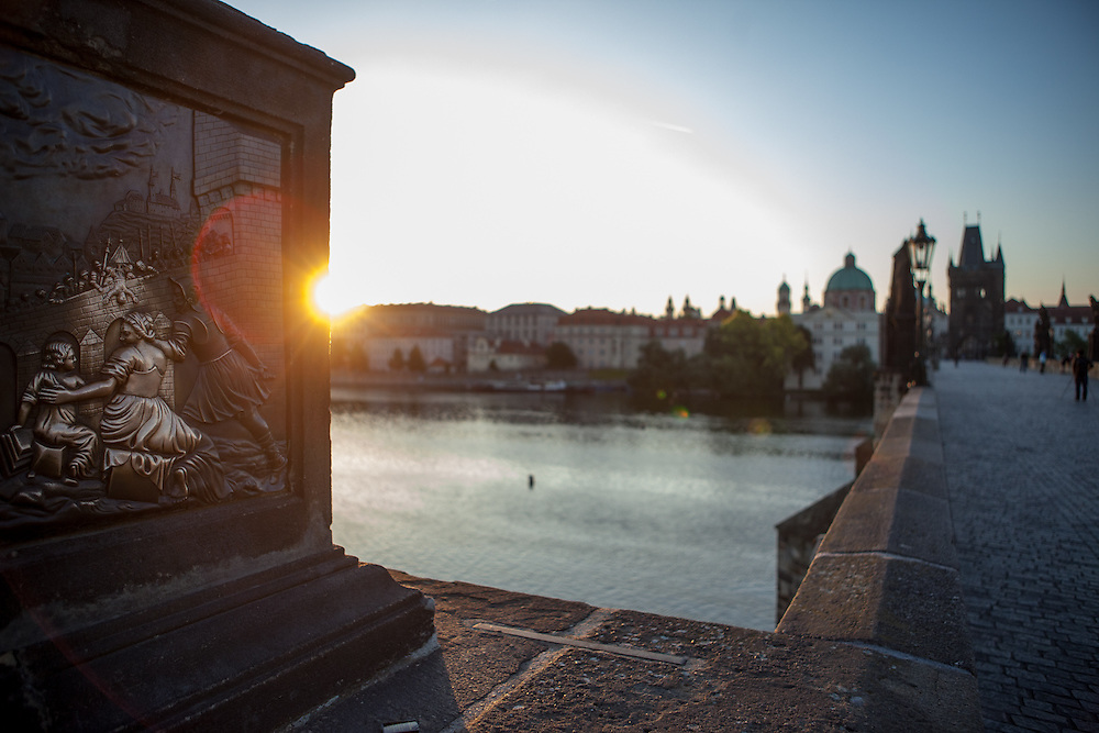 Charles Bridge and the view to Prague Old Town during sunrise at the St. John of Nepomuk Statue. Touching the statue is a Prague ritual. It is supposed to bring good luck and to ensure that you return to Prague soon.