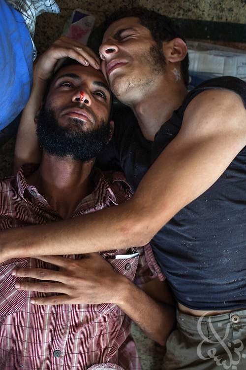Two wounded protestors cry in each others arms inside a packed field hospital at the Rabaah al-Adawiya protest camp in Nasr City during the August 14, 2013 Ministry of Interior/Police operation to clear the protest by force. The assault, which began at 7am with police moving in to seal the surrounding streets included tear gas and live fire, and there are reports of large numbers of killed and wounded protesters.
