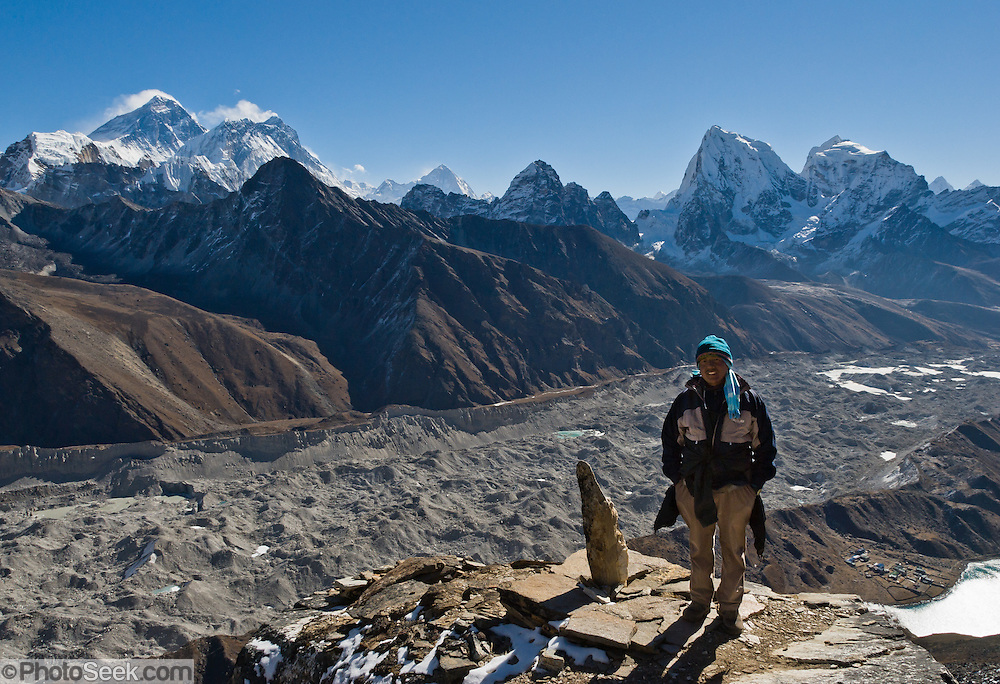 Our guide Chhatra stands on the peak of Gokyo Ri (17,580 feet) above Ngozumpa Glacier, the largest glacier in Nepal. On the upper left is Mount Everest (29,035 feet / 8850 meters elevation above sea level, from 1999 GPS measurement). On the right is the peak of Arakam Tse (21,000 feet) and Cholatse. Sagarmatha National Park was created in 1976 and honored as a UNESCO World Heritage Site in 1979.
