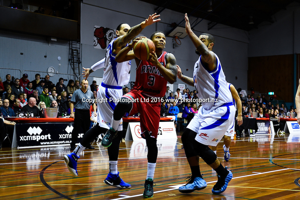 Jamie Adams of the Rams shoots though Leon Henry of the Saints and B. J. Anthony of the Saints  during the NBL Basketball Match, Canterbury Rams V Wellington Saints, Cowles Stadium, Christchurch, New Zealand. 21st May 2016. Copyright Photo: John Davidson / www.photosport.nz