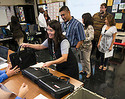 Teachers receive their laptops during the PowerUp laptop distribution and training at Austin High School, August 13, 2013.
