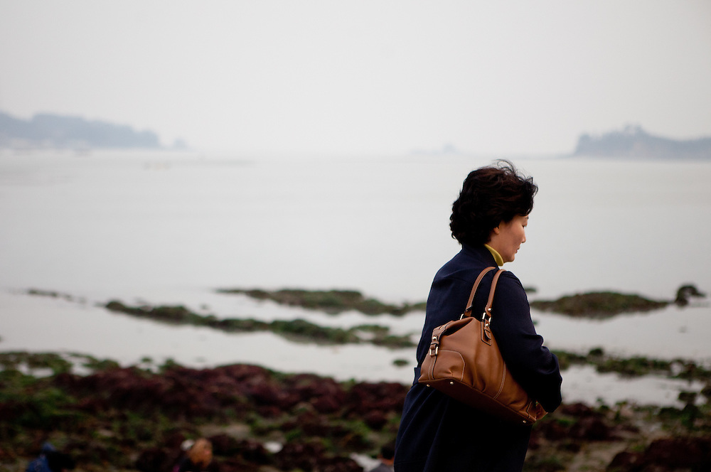 "Woman watching the already closed  ""Mysterious Sea Road"" at Hoedong shore (Jindo island) which is usually for about one and a half hour fully open. Jindo is the 3rd biggest island in South Korea located in the South-West end of the country and famous for the ""Mysterious Sea Route"" or ""Moses Miracle"" . Every spring thousands flock to the shores of Jindo to walk the mysterious route that stretches roughly three kilometers from Hoedong to the distant island of Modo (right side in the back). Materializing from the rise and fall of the tides, the divide can reach as wide as forty meters."