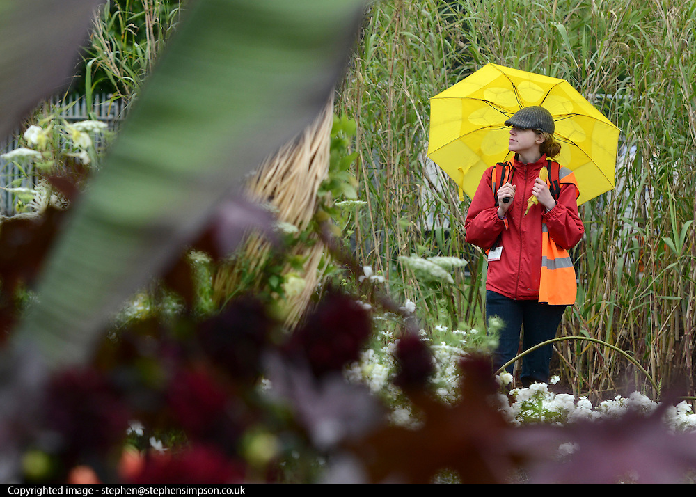 © Licensed to London News Pictures. 02/07/2012. East Molesey, UK A woman shelters from the rain under a yellow umbrella. The RHS Hampton Court Palace Flower Show 2012. The show runs 3-8 July, 2012. Photo credit : Stephen Simpson/LNP