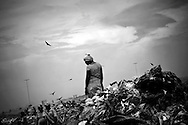 A Warao woman searches through a heap of garbage at the Cambalache dump in Ciudad Guayana, in northeastern Venezuela. In an effort to escape poverty, hunger and to be closer to health care facilities, approximately 300 Warao indigenous persons from the Delta Amacuro have settled in Ciudad Guayana. The Warao sustain themselves and their families by salvaging recyclables, clothing and discarded food in Cambalache, located minutes from downtown Ciudad Guayana. Although Warao community leaders say their quality of life is improved in comparison to the conditions in the Delta, the Warao are still plagued by hunger and diseases consequential of the unsanitary conditions of living and working in Cambalache.