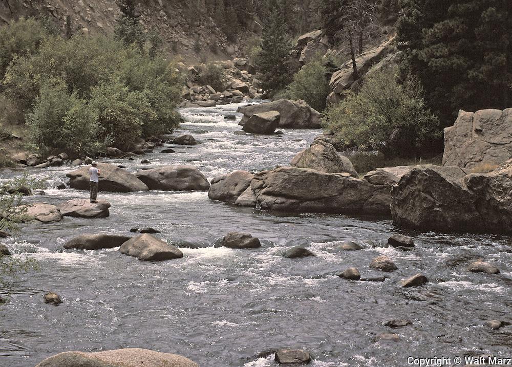 Fisherman working mountain stream in Colorado Rockies