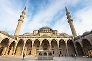 Tourists in collonaded courtyard of Suleymaniye Mosque in Istanbul, Republic of Turkey