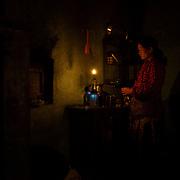 A la lueur d'une lampe, Katmandou, N&eacute;pal 2009.<br /> <br /> Cette jeune femme, enceinte de cinq mois s'appelle &laquo;&nbsp;Sandh&agrave;&nbsp;&raquo; qui signifie &laquo;&nbsp;Soleil&nbsp;&raquo; en n&eacute;palais. Elle pr&eacute;pare le d&icirc;ner pour son mari, &agrave; la lueur d'une lampe &agrave; p&eacute;trole. La cuisine est aussi la chambre &agrave; coucher. Le jeune couple vit dans 9m&sup2; dans le centre de Katmandou, souvent sujet &agrave; des coupures d'&eacute;lectricit&eacute;.