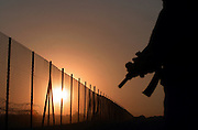 An Israeli security guard patrols along the partcially built fence along the western edge of the West Bank city of Qalqilyia  at dawn June.17,2003.The Israeli goverment's goal is to cut Israel off from the West Bank with a fence 370 miles long,claiming that the barrier will help prevent suicide bombers.Only about 20 miles are finished and another 100 miles are partly built. Israel has seized thousands of acres of Palestinian farm land to builf the barrier.Because the fence veers into the West Bank, about 95,000 Pale4stinians or 4.5 percent of the Palestinian zones's population could end up living in fenced in enclaaves off limits to nonresidents according to studies by the European Union,U.S. goverment,World Bank and International Monetary Fund.(Photo by Heidi Levine/Sipa Press).