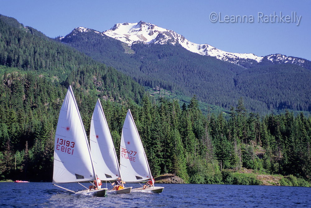 Three laser sailboats race on Alta Lake, Whistler, BC Canada.