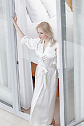 Beautiful young woman standing at balcony doorway
