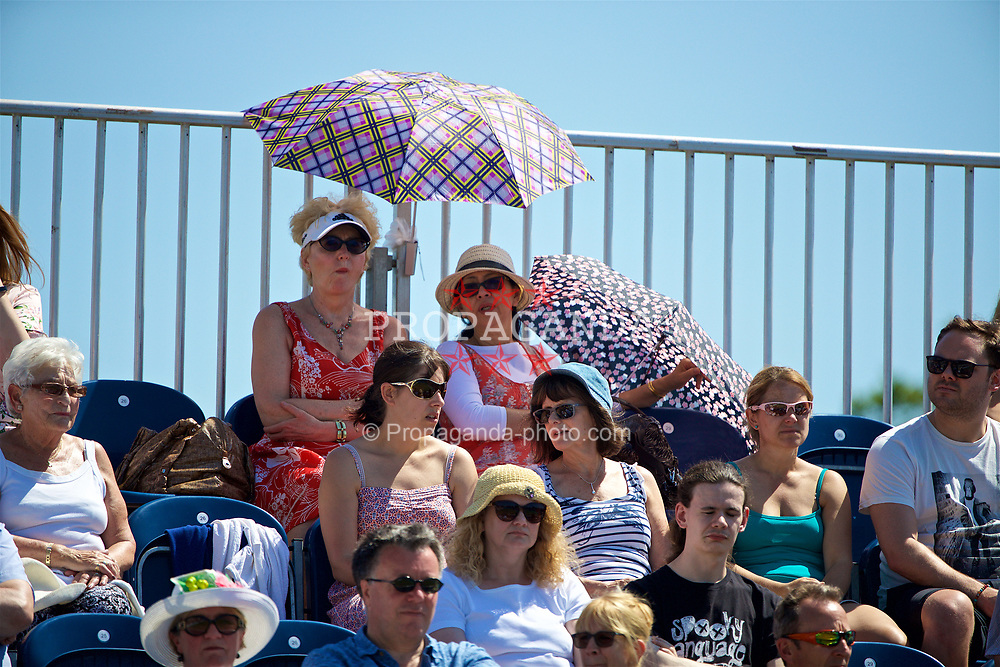 LIVERPOOL, ENGLAND - Saturday, June 17, 2017: Spectators use an umbrella to shield them from the sun during Day Three of the Liverpool Hope University International Tennis Tournament 2017 at the Liverpool Cricket Club. (Pic by David Rawcliffe/Propaganda)