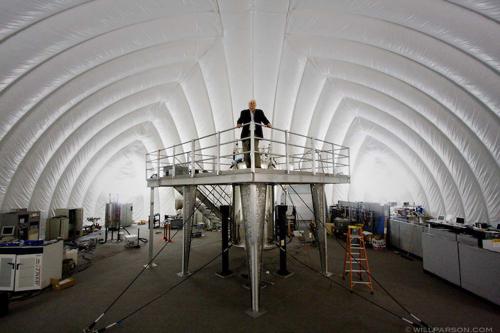 "Stanley Opella, director of the Nuclear Magnetic Resonance Resource Lab at UC San Diego poses in a special structure known as ""The Bubble"" which is designed without metal to avoid interference when experiments are run."