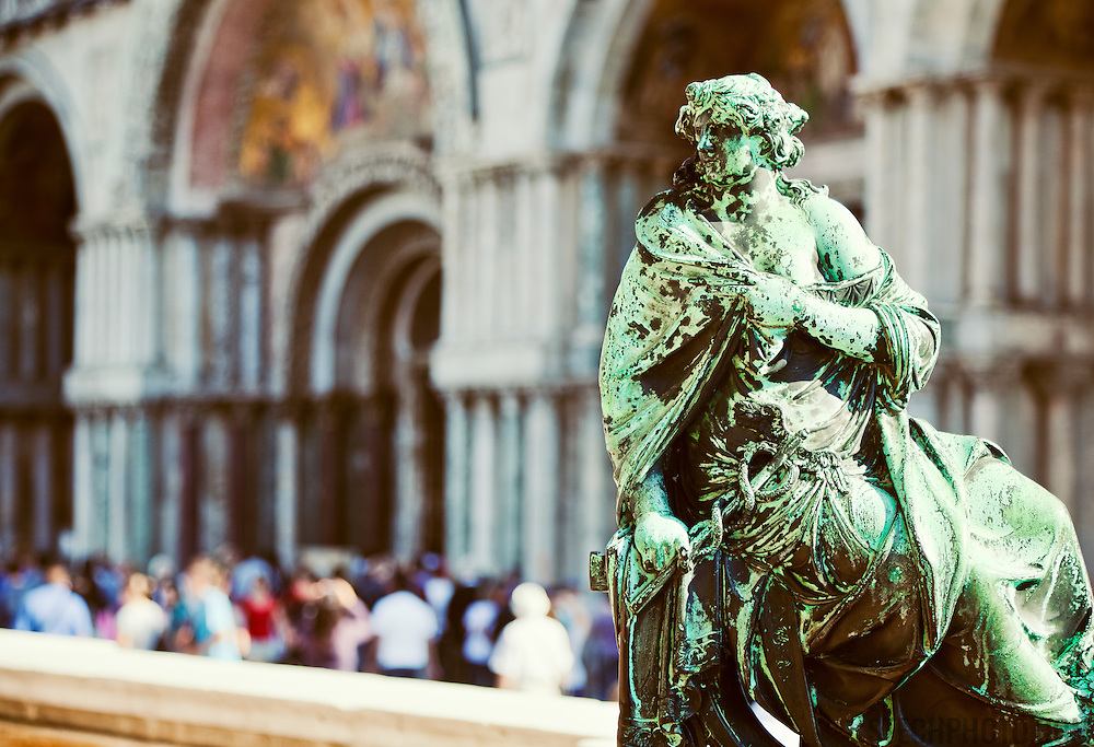 A statue in front of the crowds visiting St. Mark's Square and Basilica (Basilica di San Marco) in Venice, Italy.