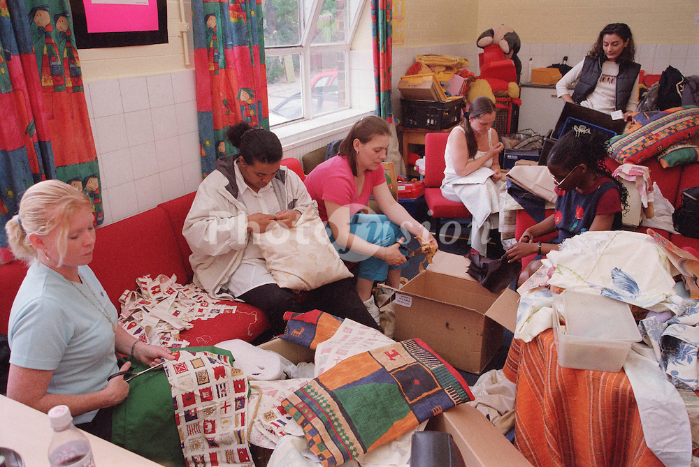 Multiracial group of parent volunteers working together to make cushion covers,