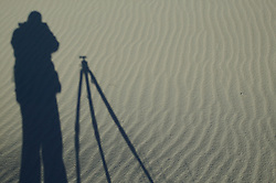 A photographer and tripod's shadow appear on the sands of White Sands National Monument.