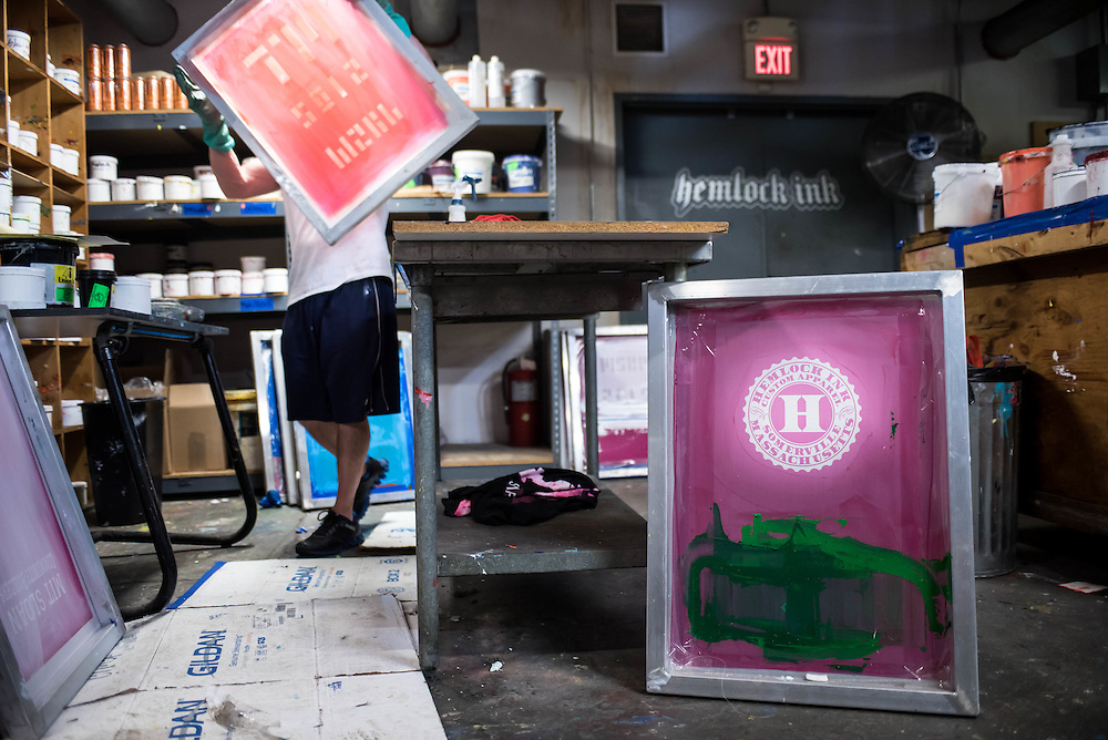 A screen printer at work in the Hemlock Ink shop in Somerville, MA.
