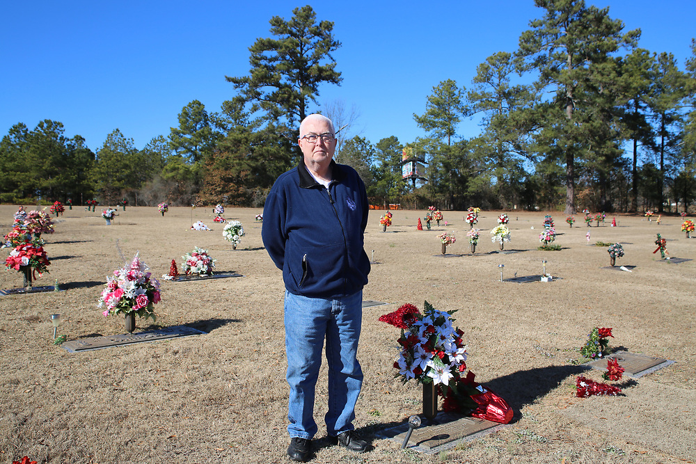 Jay Carroll by his late wife's grave at the cemetery where all the Irish Travellers are buried a few miles from Murphy Village. <br />