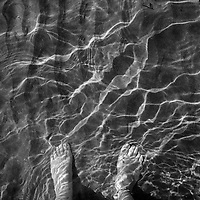A woman's feet in the sand, through the crystal clear water, in the beach