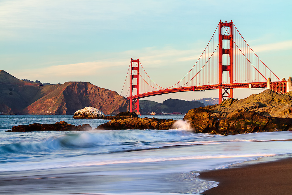 The Golden Gate Bridge viewed from Marshall Beach at sunset in San Francisco as the waves crash into the shoreline rocks.