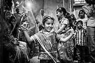 A young girl dances in the street after having been part of a parade of women celebrating the Gargaun festival in Jodhpur. This festival honors the union of the god Shiva with the goddess Parvati. Women celebrate by dressing very colorful and carrying pots of sacred water in parades through the streets. Jodhpur, Rajhastan, India. / Una niña baila en las calles después de haber participado en un desfile de mujeres por el festvial de Gargaun. Este festival honra la unión del dios Shiva con la diosa Parvati. Las mujeres lo celebran vistiéndose de una manera muy vistosa y cargando recipientes de agua sagrada en desfiles por las calles. Jodhpur, Rajastán, India.