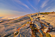 Whispy clouds above cadillac mountain with small tree at top. Foreground full of granite. Fall color in foliage.