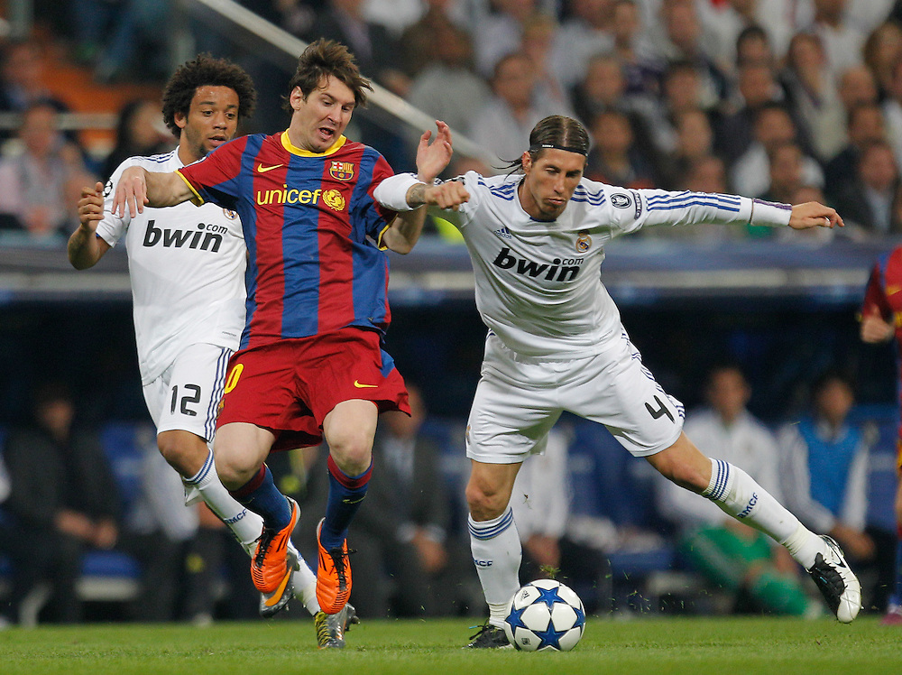 FC Barcelona's Lionel Messi from Argentina, center, vies for the ball with Real Madrid's Marcelo from Brazil, left, and Sergio Ramos, right, during a semi final, 1st leg, Champions League soccer match at the Santiago Bernabeu stadium in Madrid, Wednesday, April 27, 2011.