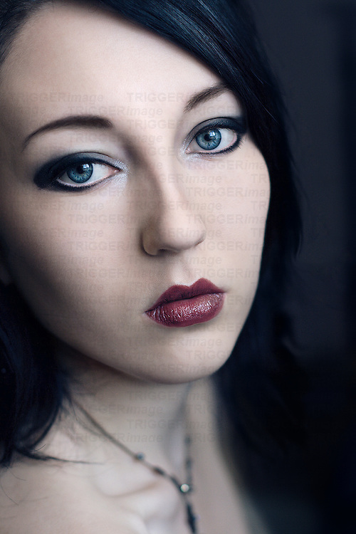 Portrait of a young woman with black hair blue eyes and pale skin looking into the camera with simple background.