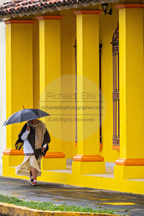 A woman with an umbrella walks past a colorful colonnade style building in Tlacotalpan, Veracruz, Mexico. The tiny town is painted a riot of colors and features well preserved colonial Caribbean architectural style dating from the mid-16th-century.