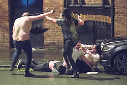 © Licensed to London News Pictures . 01/01/2017 . Manchester , UK . A shirtless man and a woman clash as another man lies in the gutter . A fight involving several men and women spills over on to St Mary's Parsonage . People on a night out in Manchester City Centre , after midnight on January 1st 2017 . Photo credit : Joel Goodman/LNP