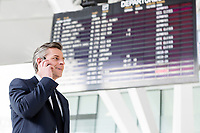 Attractive mature businessman talking on smartphone while standing against flight screen display in airport