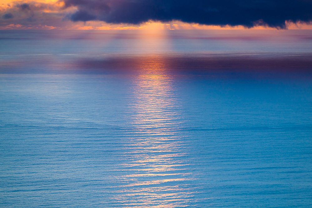 A beam of sunset light shines over the Norwegian Sea off the coast at Bunes Beach, Moskenesoya, Lofoten Islands, Norway.