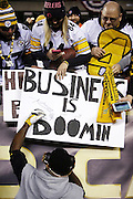 """Pittsburgh Steelers wide receiver Antonio Brown (84) signs a """"business is booming"""" sign for a fan before the NFL AFC Wild Card playoff football game against the Cincinnati Bengals on Saturday, Jan. 9, 2016 in Cincinnati. The Steelers won the game 18-16. (©Paul Anthony Spinelli)"""