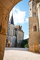 View through an archway to the inner courtyard of Chateauneuf-en-Auxois, France.
