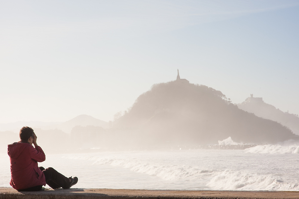 Woman covering her eyes and listening to the waves in San Sebastian (Spain)