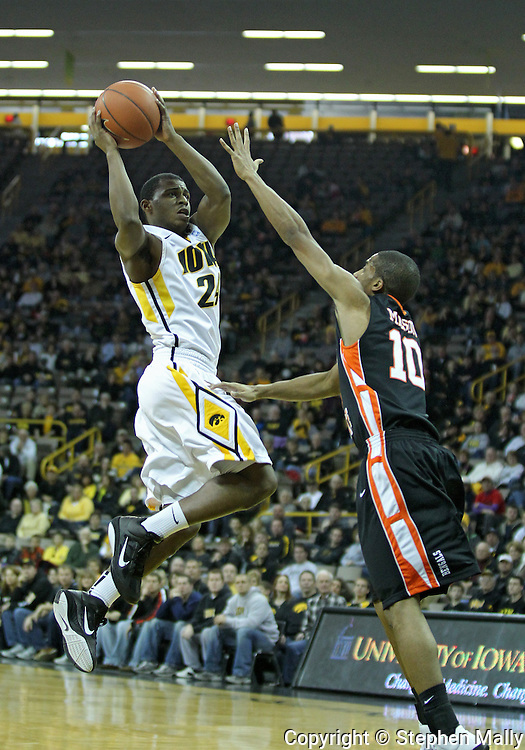 December 04 2010: Iowa Hawkeyes guard Bryce Cartwright (24) goes through the air by Idaho State Bengals guard Nick Mason (10) during the first half of their NCAA basketball game at Carver-Hawkeye Arena in Iowa City, Iowa on December 4, 2010. Iowa won 70-53.