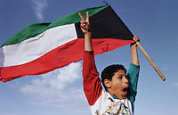 A young boy celebrates independence day in Kuwait city, 1998. After the first Gulf War (1990-91) the US and UK continued air strikes on targets in Iraq and a bulid up of troops in the Kuwaiti desert known as Operation Desert Fox.