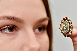 "© Licensed to London News Pictures. 15/06/2017. London, UK. A staff member views an intricate ring called ""Bague de forme ovale.  Portrait of Dora Maar"", 1936-9, by Pablo Picasso (estimate GBP300-500k).  Preview of Impressionist and Modern art sale, which will take place at Sotheby's New Bond Street on 21 June.  Photo credit : Stephen Chung/LNP"