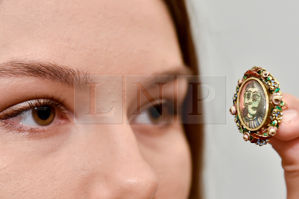 """© Licensed to London News Pictures. 15/06/2017. London, UK. A staff member views an intricate ring called """"Bague de forme ovale.  Portrait of Dora Maar"""", 1936-9, by Pablo Picasso (estimate GBP300-500k).  Preview of Impressionist and Modern art sale, which will take place at Sotheby's New Bond Street on 21 June.  Photo credit : Stephen Chung/LNP"""