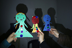 Syrian refugee children hold paper puppets made during an art therapy class with psychologist Lina Zaarour at the Caritas centre in the Bekaa Valley region of Lebanon. The classes form part of the psychological care given to the children to help them overcome the trauma of war using arts, crafts and games.