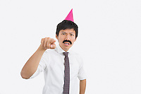 Angry businessman wearing party hat pointing in office