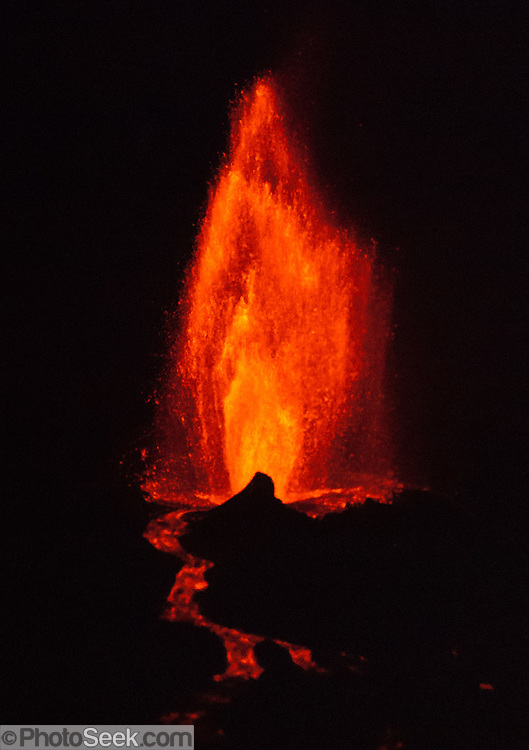 "April 21, 2009: La Cumbre volcano erupts a fountain of lava creating a red river flowing into the Pacific Ocean, expanding Fernandina (Narborough) Island, in the Galápagos Islands, a province of Ecuador, South America. This eruption cycle started April 10, 2009 after 5 years of quiet. Fernandina Island was named in honor of King Ferdinand II of Aragon, who sponsored the voyage of Columbus. Fernandina is the youngest and westernmost island of the Galápagos archipelago, and has a maximum altitude of 1,494 metres (4,902 feet). Tourists are allowed to visit Punta Espinosa, a narrow stretch of land where hundreds of Marine Iguanas gather largely on black lava rocks. The Flightless Cormorant, Galápagos Penguins, Pelicans and Sea Lions are abundant on this island of lava flows and Mangrove Forests. Published in ""Light Travel: Photography on the Go"" book by Tom Dempsey 2009, 2010."